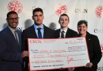 "four people hold up a 5,000 dollar check for their company called ""germ 3 solutions"""