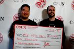 "Two men hold up their 10,000 dollar check for a company called ""my gym pals"""