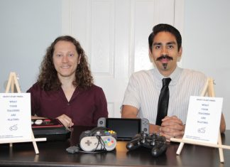"""Altman and Cardenas sit at a desk filled with video game accessories and a card that says, """"what your teachers are playing"""""""