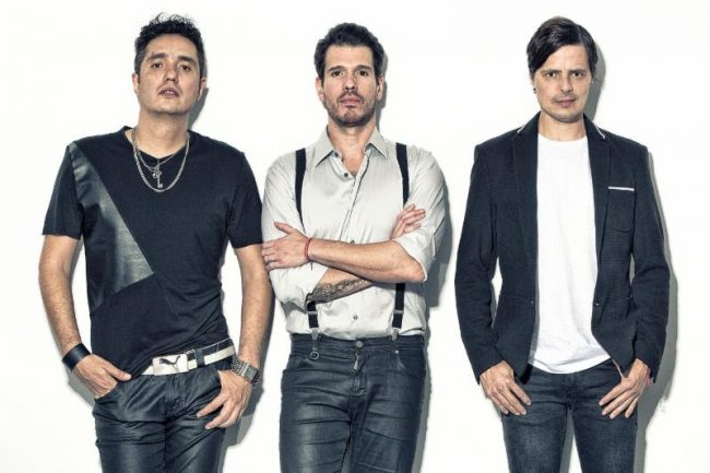 Mexican rock band members pictured, three men in their mid-thirties wearing matching navy blue and white oufits