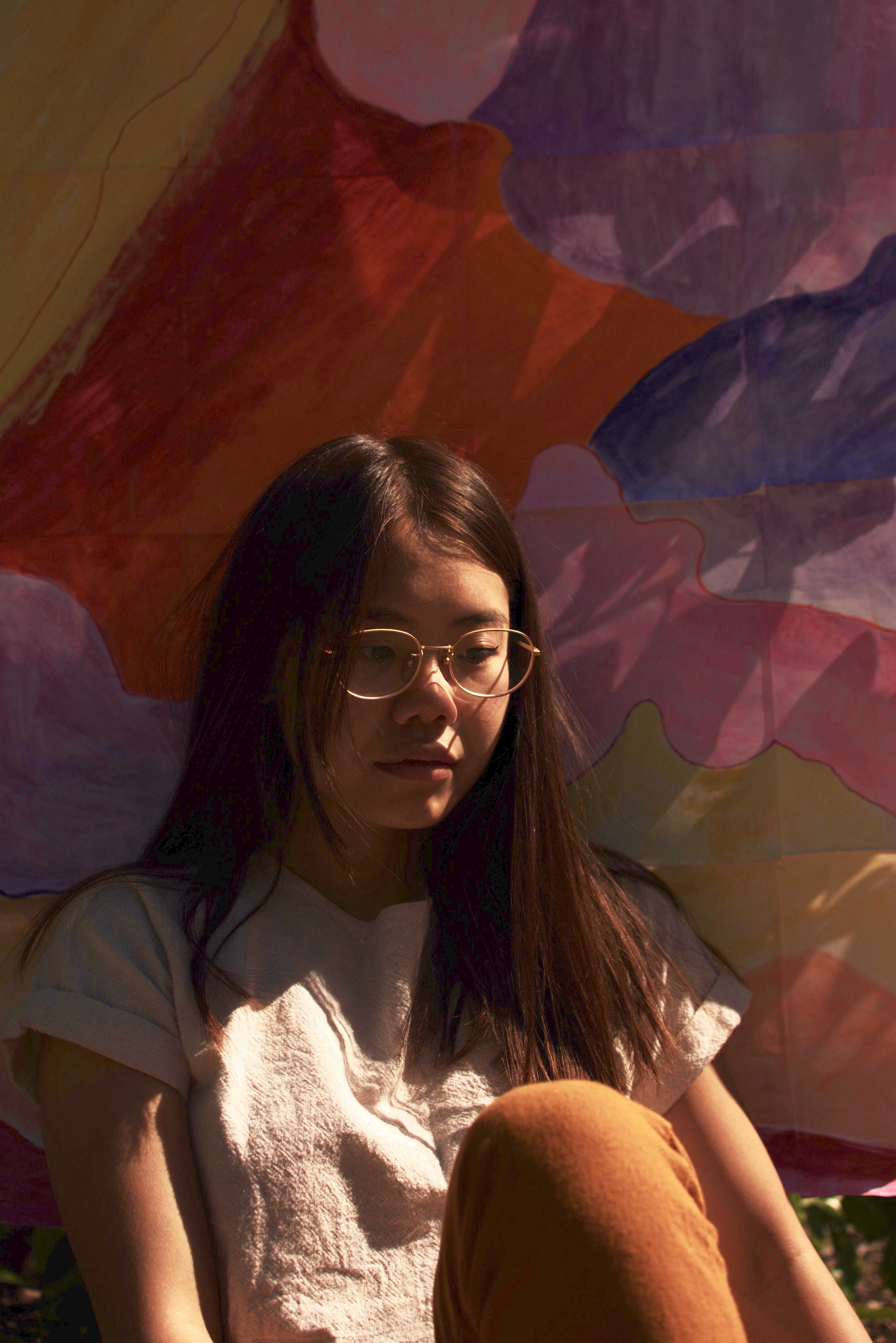 Trina Teoh sits before her water-color artwork. Photo Credit: Andrew Anguilar