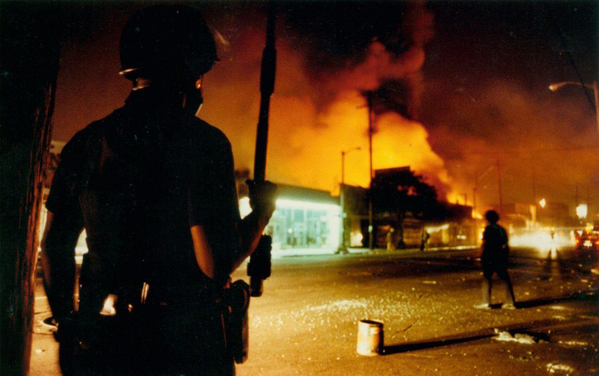 Police+officer+pictured+at+the+scene+of+riots+behind+a+large+cloud+of+smoke+near+a+shopping+center