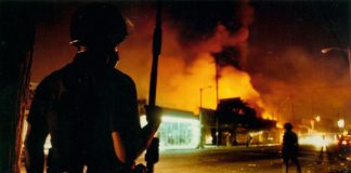 Police officer pictured at the scene of riots behind a large cloud of smoke near a shopping center