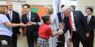 donald trump and betsey devos shakes hands with students and teachers in a classroom
