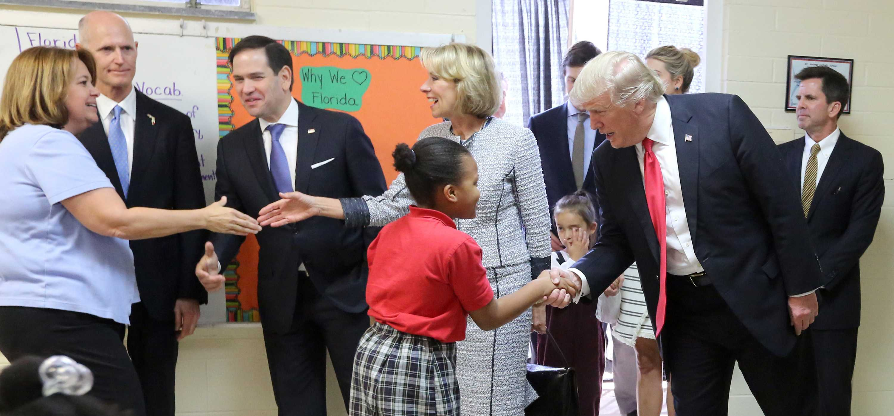 President Donald Trump greets fourth grader Janayah Chatelier as U.S. Secretary of Education Betsy DeVos greets St. Andrew Catholic School fourth grade teacher Jane Jones on March 3, 2017, in Orlando, Fla. Looking on is Florida governor Rick Scott, second from left, Florida senator Marco Rubio, third from left, and John Kirtley, far right, a tax-credit scholarship proponent. (Joe Burbank/Orlando Sentinel/TNS)