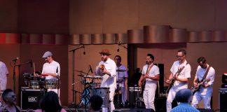 Jungle Fire band members wear matching all white ensembles and concert-goers dance to the music