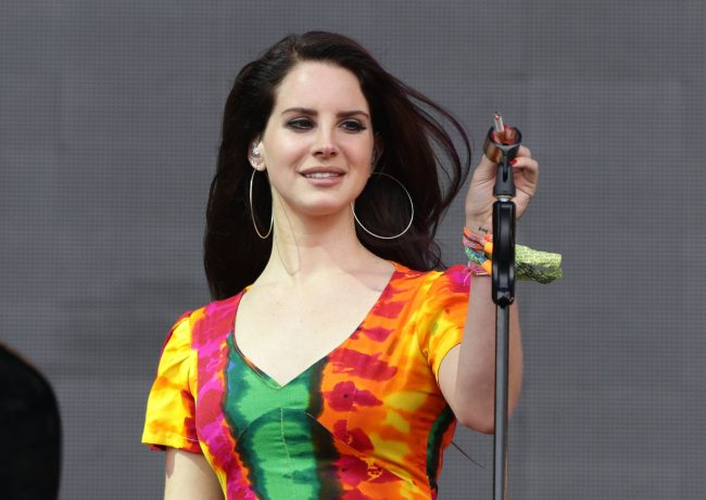 Lana del Rey pictured in a bright tie-dye dress putting her cigarette in the mic-holder