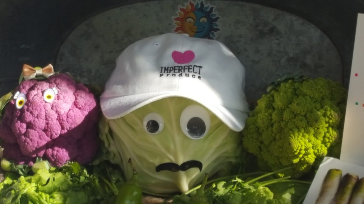 Cabbage+pictured+in+the+center+of+other+vegetables+with+eyes+glued+on+and+a+hat+that+says+imperfect+produce