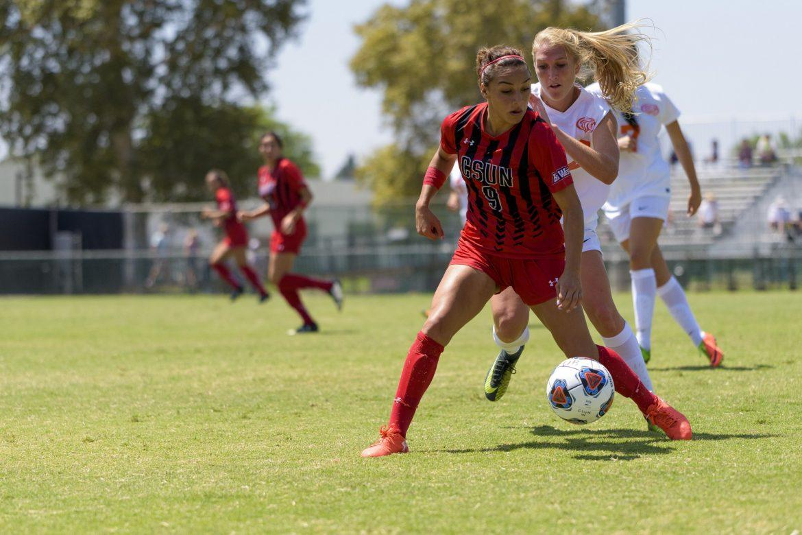 csun+soccer+player+looks+focused+as+she+blcoks+the+other+team%27s+player