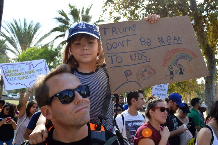 Little girl sits on her dad's shoulders at protest with a sign that says,