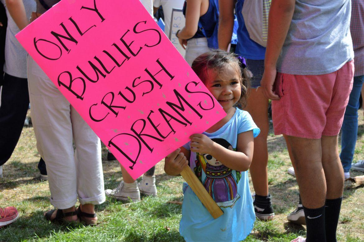 Cia+Reyes%27+daughter+peaking+out+from+behind+her+sign+at+LA%27s+DACA+protest.+Photo+credit%3A+Makenna+Sievertson