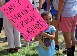 """young girl (no older than 4) holds up a sign that says, """"only bullies crush dreams"""""""