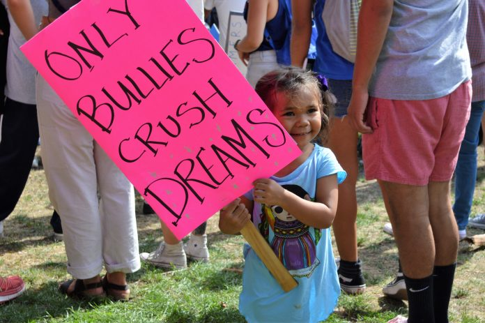 young girl (no older than 4) holds up a sign that says,