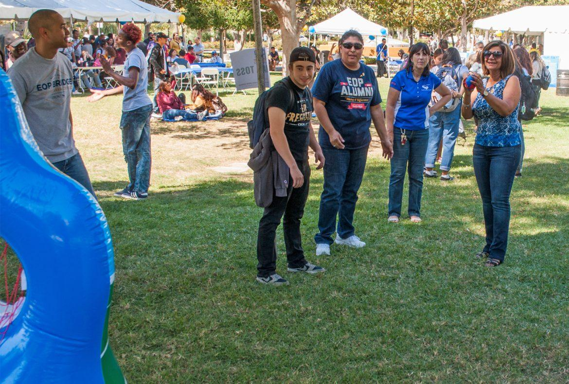 EOP director, Shiva Parsa, plays footall toss at the Eop 48 year celebration on the Bayramian Hall Lawn Photo credit: Brandon Ilano