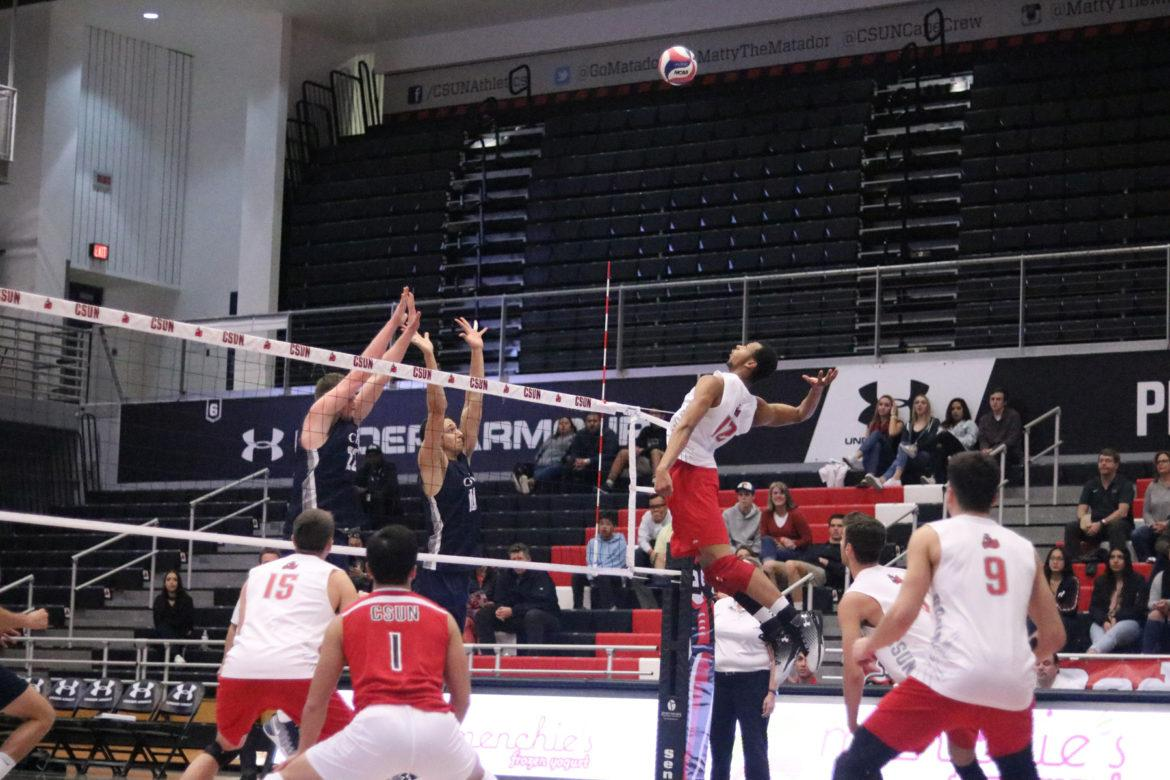 CSUN's junior opposite hitter, Arvis Greene Jr., spikes the ball against a double block in the first set on Friday, Feb. 24, at the Matadome. Photo Credit: Lauren Valencia/The Sundial