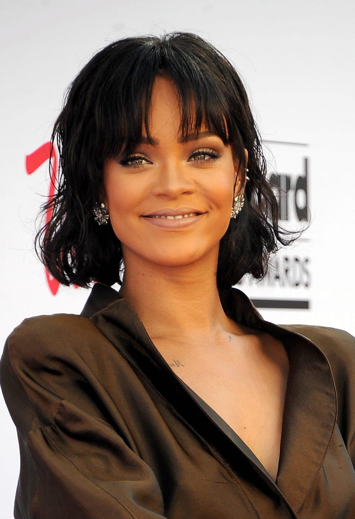 Rihanna+pictured+smiling%2C+shes+wearing+a+dark+green+jacket+and+has+short+black+hair+with+bangs