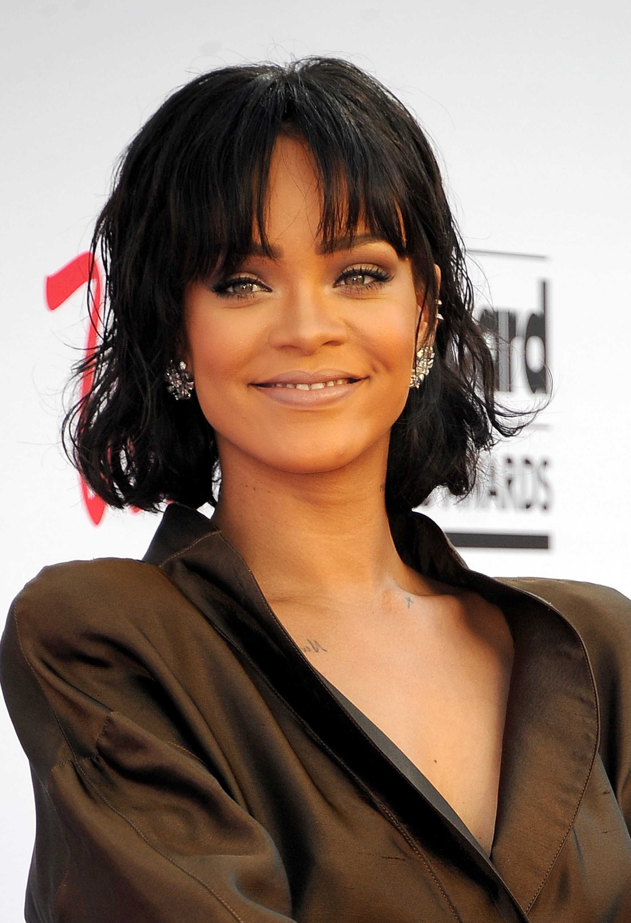 Rihanna pictured smiling, shes wearing a dark green jacket and has short black hair with bangs