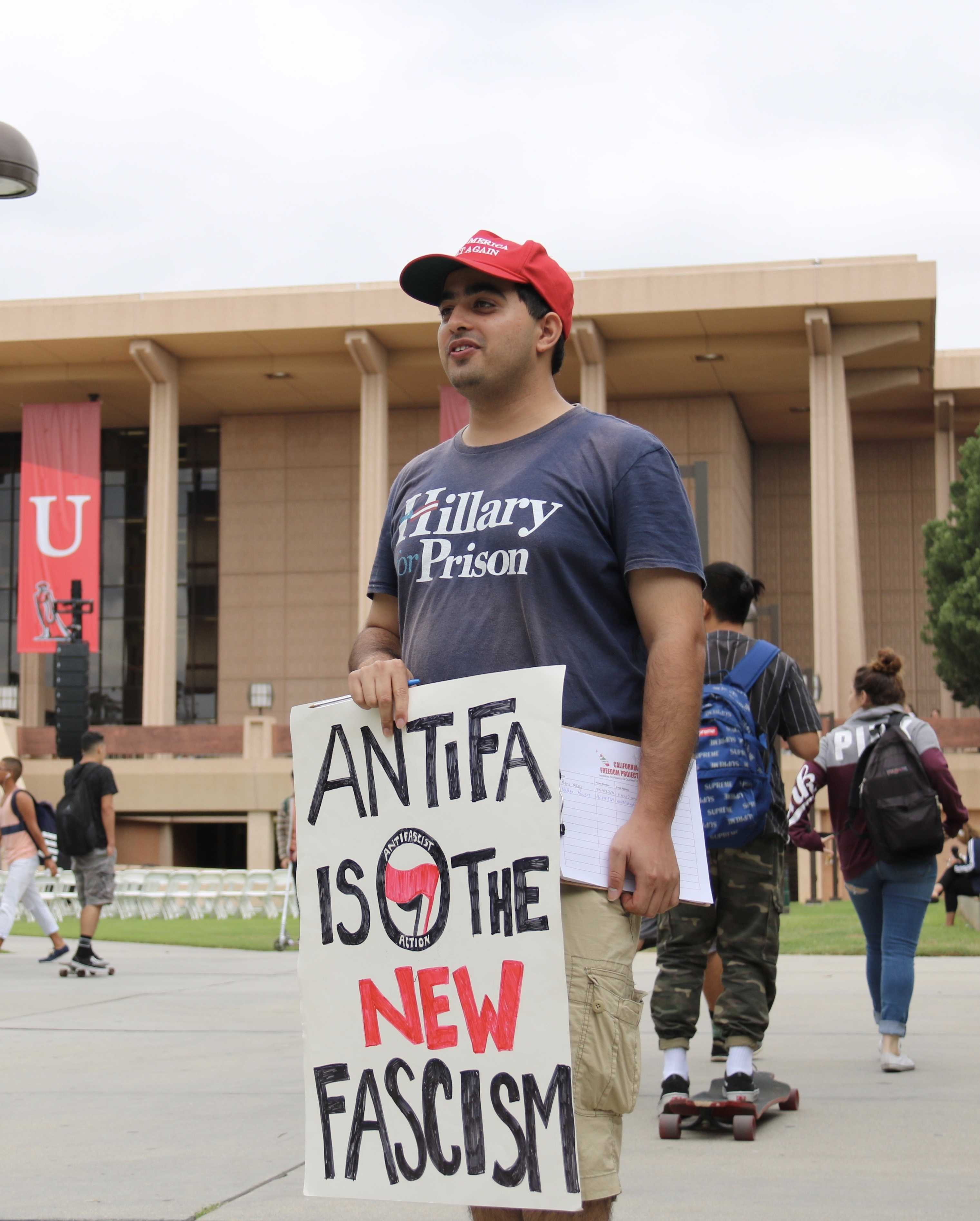 "Man pictured on the Oviatt lawn wearing a shirt that says, ""Hillary for Prison"" he is holding a sign up that says, ""Antifa is the new facism"""