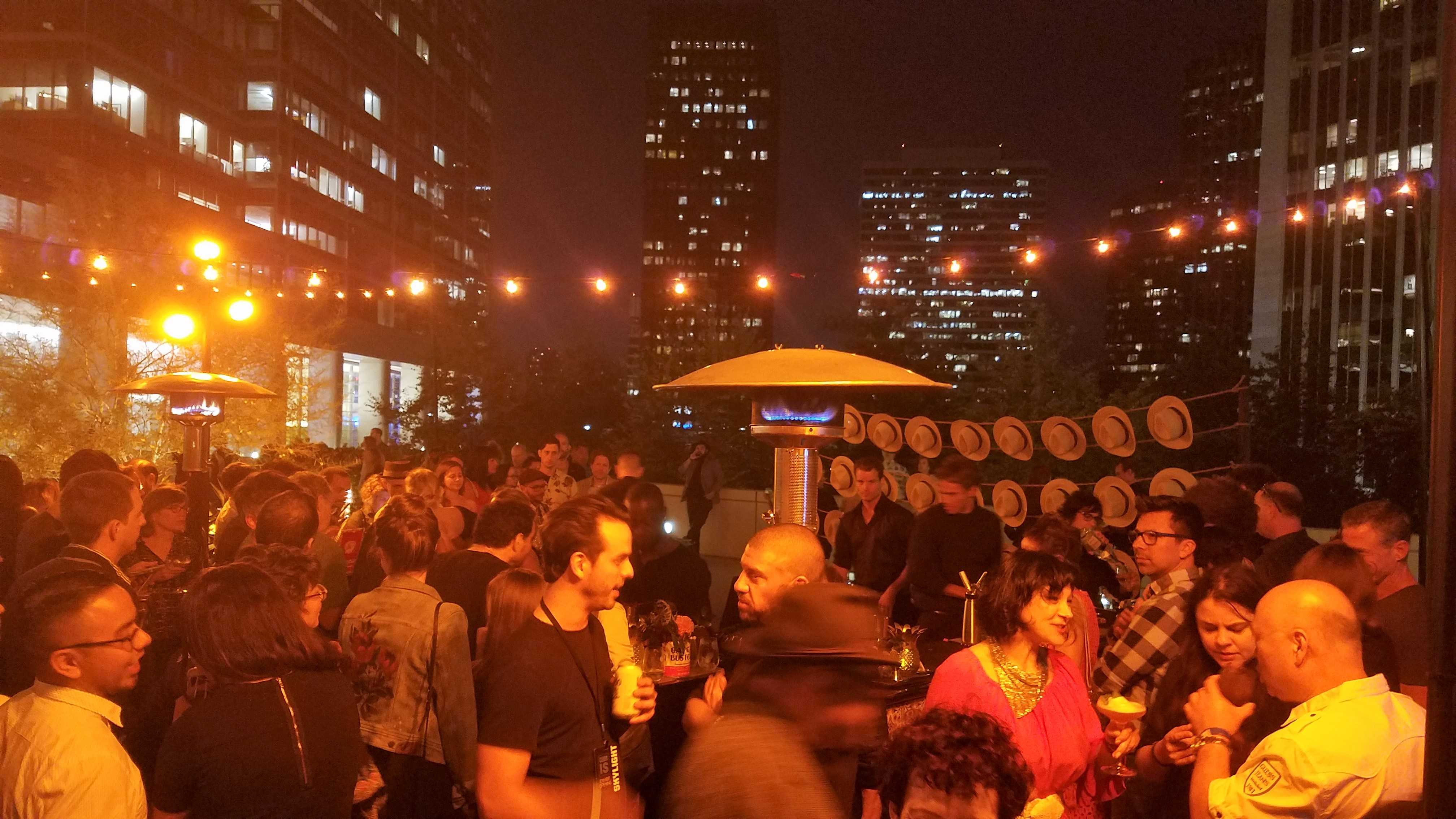 Large group of people pictured on a rooftop chatting and drinking