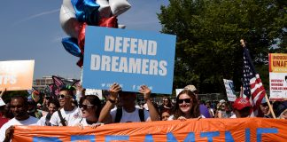 """protesters hold up several signs, on of them which reads, """"dreaming"""" and another says, """"defend dreamers"""""""