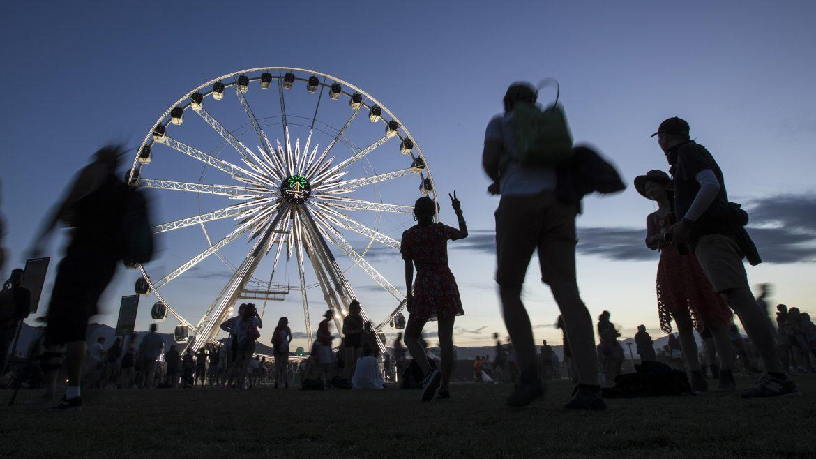 ferris wheel pictured surrounded by people at twilight
