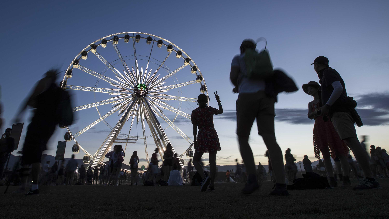 blurry people walk near giant ferris wheel