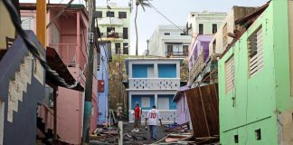Photo shows two men walking through an allyway of partially destroyed houses