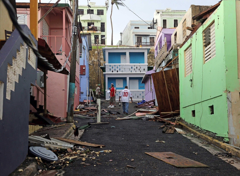 A man walks near colorful damaged buildings.  Residents of San Juan's