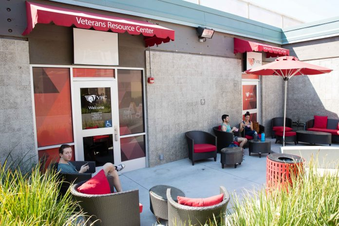 Exterior of veteran's resource center pictured with red awnings and plenty of chairs