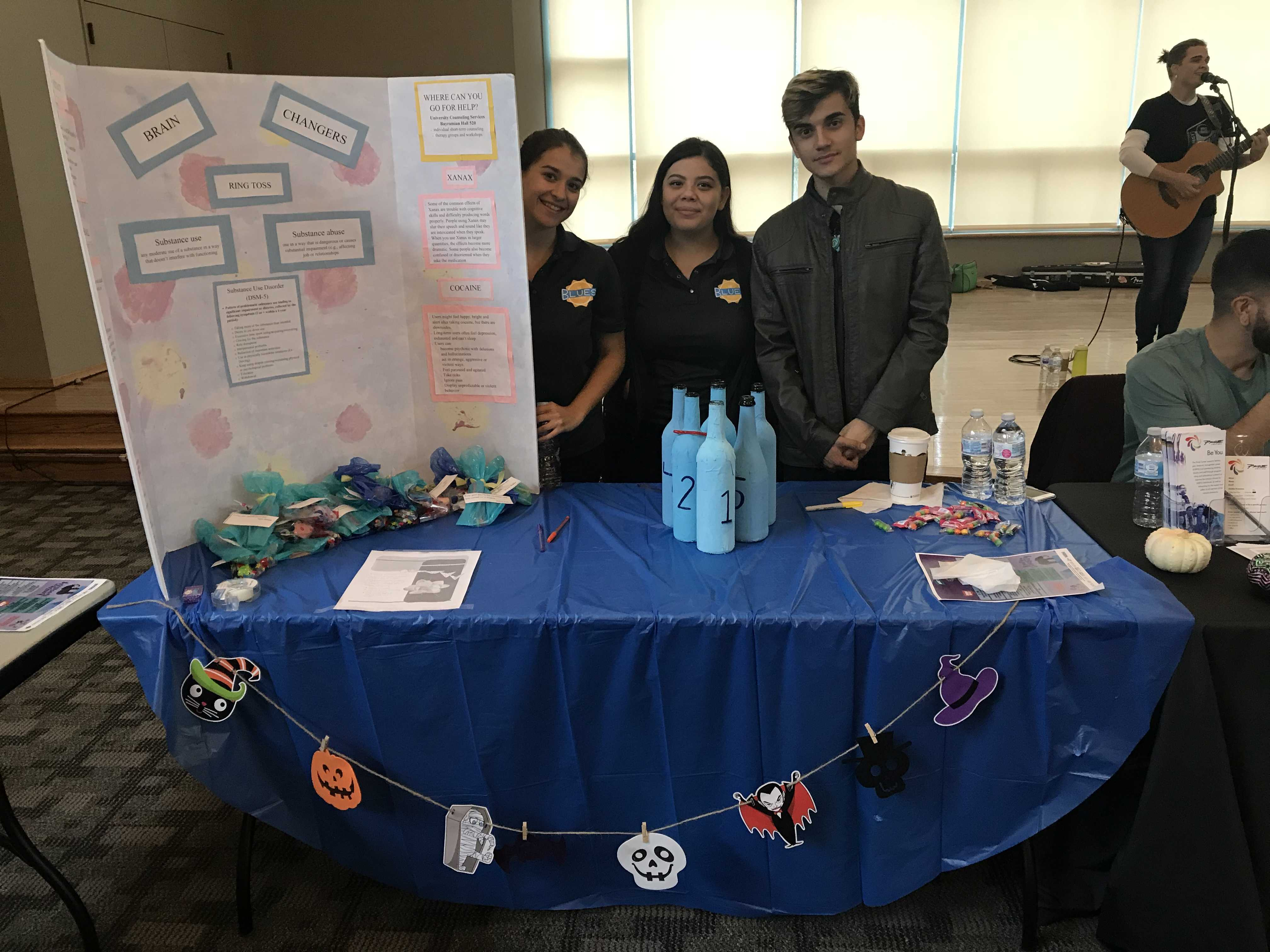Left to right: Alyssa Peter, Celeste Mar, and Walter Linares giving the community information on brain chargers like substance abuse. Photo credit: Nicole Merino