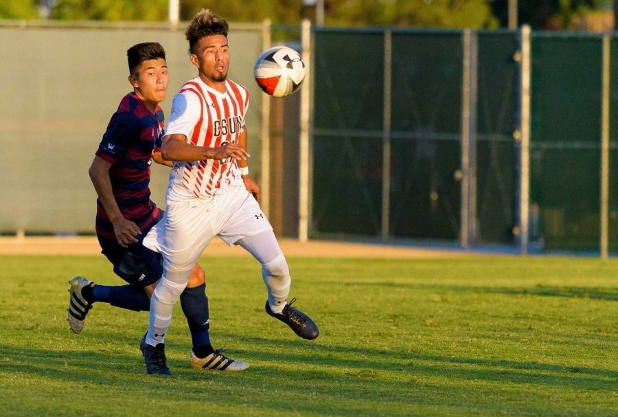 CSUN male soccer team in white red and white playing soccer