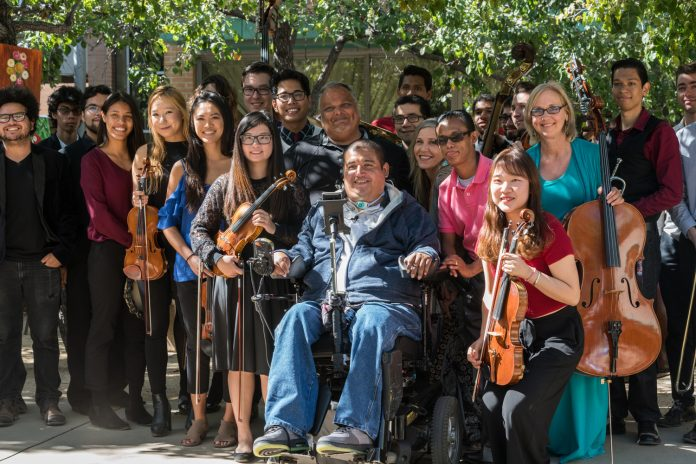 musicians posing for a photo with violins and cellos
