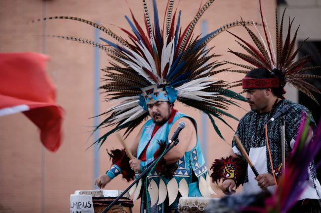 men in blue black and red traditional feathered outfit performing with drums