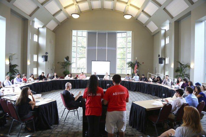 man and woman in red shirts standing in front of round table