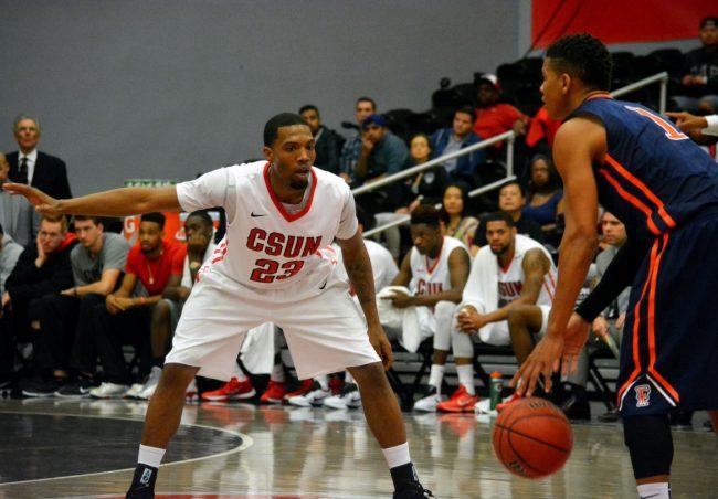 CSUN male athlete in white uniform playing basketball