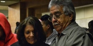 woman wearing black and man wearing grey smiling together