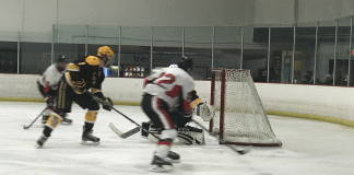 CSUN hockey player in white red and black playing against black and yellow team