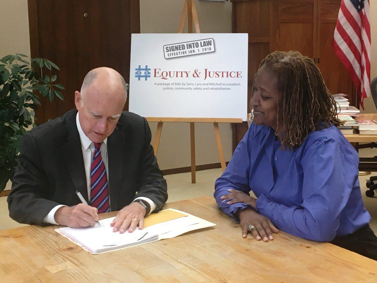 California State Senator Holly J.  Mitchell looks on approvingly as Governor Jerry Brown signs nine of her #Equity&Justice bills aimed at reforming the juvenile justice system