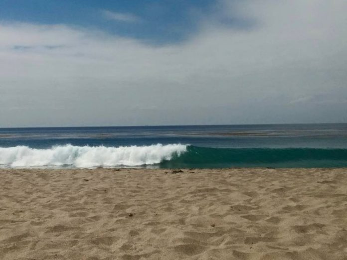 image of brown sand and blue wave