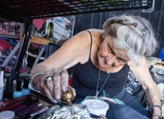 elderly woman painting colorful rock