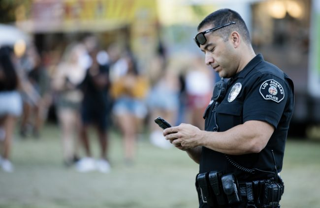 male police officer with black sunglasses holding phone