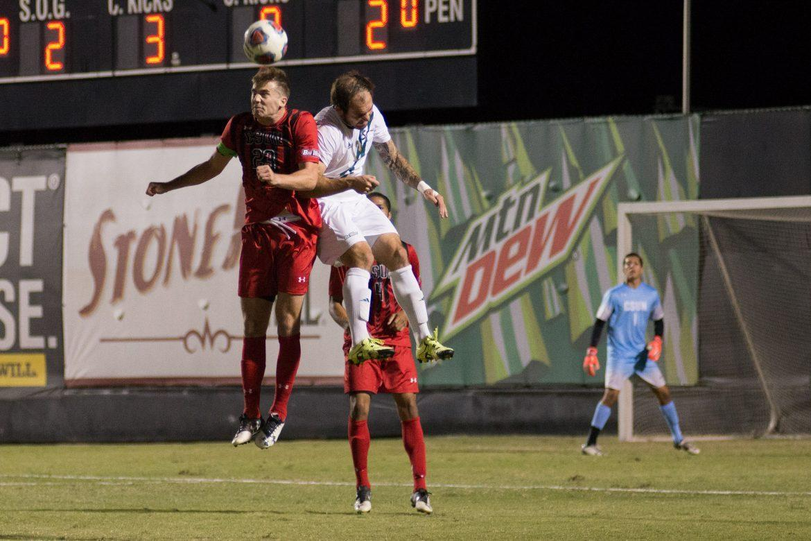 csun+male+soccer+player+in+red+jumping+alongside+player+in+white
