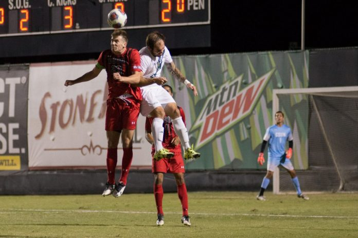csun male soccer player in red jumping alongside player in white