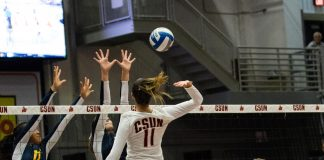 CSUN volleyball player jumping to hit the ball