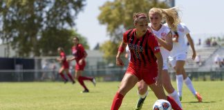 CSUN soccer player in red defending the ball