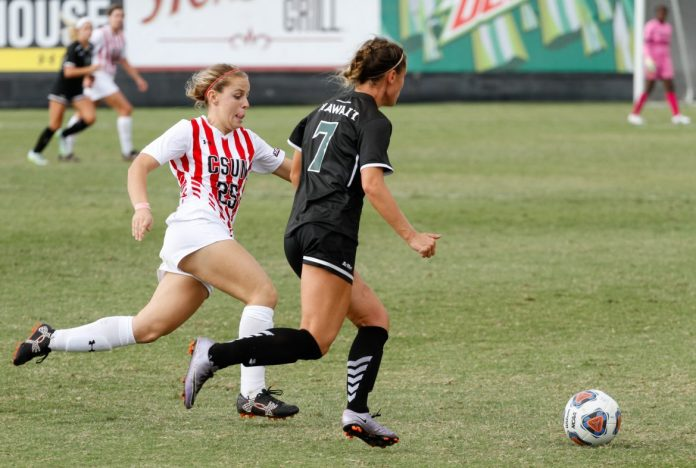 CSUN female soccer player in white and red running with determined face