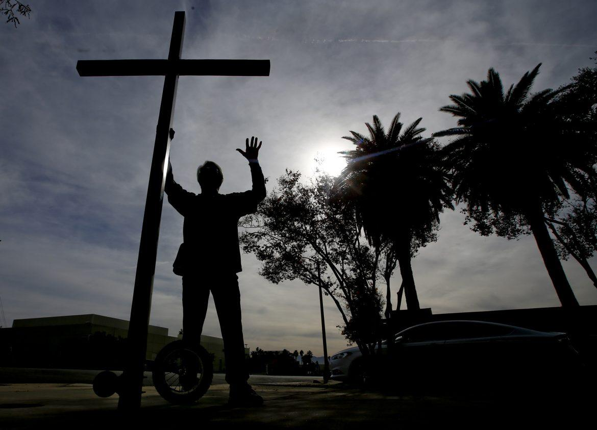 One week after the mass shooting at the Inland Regional Center in San Bernardino, Calif., self-proclaimed street evangelist Tom Alexander prays in front of the San Bernardino Police Department with his 10-foot cross on wheels on Wednesday, Dec. 9, 2015. (Mark Boster/Los Angeles Times/TNS)