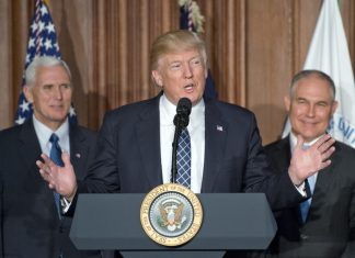 president donald trump in black and white suit speaking at a podium