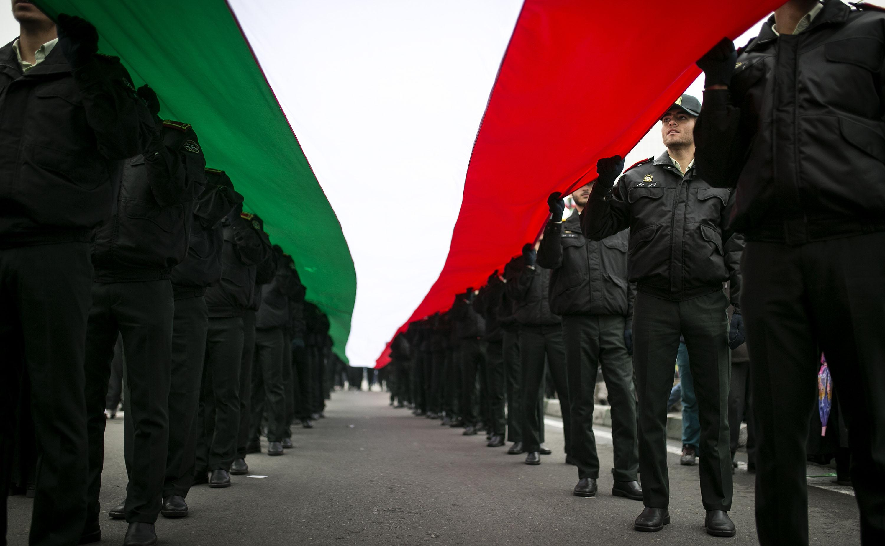 Iranian policemen hold a national flag of Iran during a rally marking the 38th anniversary of the victory of the Islamic revolution in 1979 on Feb. 10, 2017 in Tehran, Iran. (Ahmad Halabisaz/Xinhua/Zuma Press/TNS)