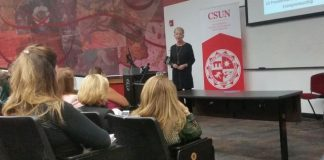 woman in black dress with red CSUN logo behind her speaks to audience